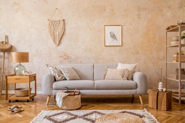 デザイングレーのソファ、木製のコーヒーテーブル、棚、キューブ、カーペット、籐のプーフ、植物、額縁、テーブルランプ、家の装飾のエレガントなアクセサリーを備えたリビングルームのインテリアのスタイリッシュなスカンジコンポジション。