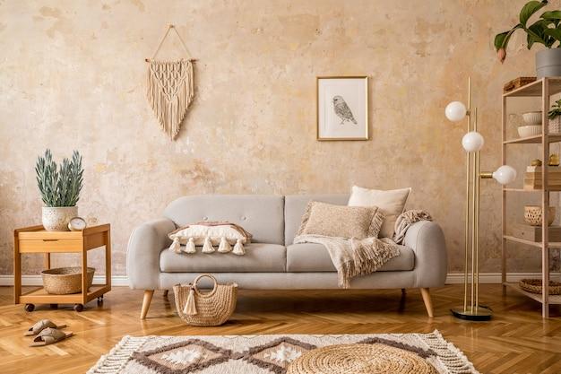 Стильная композиция scandi в интерьере гостиной с дизайнерским серым диваном, деревянным журнальным столиком, полкой, кубиком, ковром, пуфом из ротанга, растениями, рамкой для фотографий, настольной лампой и элегантными аксессуарами в домашнем декоре.