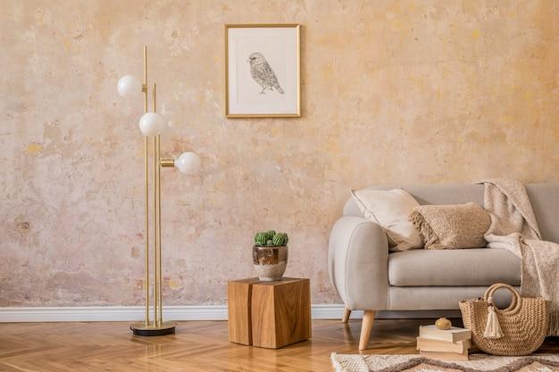 디자인 그레이 소파, 목재 커피 테이블, 선반, 큐브, 카펫, 등나무 푸프, 식물, 액자, 테이블 램프 및 가정 장식의 우아한 액세서리가있는 거실 인테리어의 세련된 스칸디 구성.