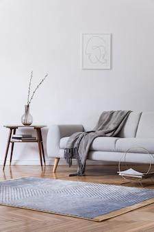 Стильный скандинавский интерьер домашнего пространства с дизайнерским серым диваном, деревянным столом в стиле ретро, рамкой для плаката, украшением, ковром и личными аксессуарами в элегантном домашнем декоре.