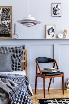 Стильный интерьер спальни в скандинавском стиле с дизайнерским стулом, растением, рамками для картин, книгой, часами и украшениями, ковром, красивыми простынями, одеялом и подушками в современном домашнем декоре.