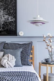 Стильный интерьер спальни в скандинавском стиле с дизайнерским журнальным столиком, макетами рамок для плакатов, книгой, часами, декором, личными аксессуарами, красивыми простынями, одеялом и подушками.