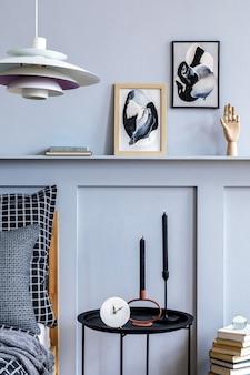세련된 스칸디나비아 침실 인테리어에는 디자인 커피 테이블, 모의 포스터 프레임, 책, 시계, 장식, 개인 액세서리, 아름다운 침대 시트, 담요 및 베개가 있습니다.