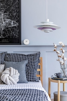 Stylish scandinavian bedroom interior with design coffee table, mock up poster frames, book, clock, decoration, personal accessories, beautiful bed sheets, blanket and pillows.