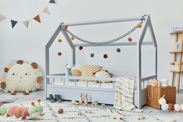 クリエイティブな木製のベッド、枕、木製の棚、ぬいぐるみと木のおもちゃ、ぶら下がっているテキスタイルの装飾が施されたスタイリッシュなスカンジナビアの子供部屋。灰色の壁、床にカーペット。レンプレート。