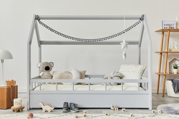 創造的な木製のベッド、木製の立方体、ランプ、木製の棚、ぬいぐるみと木のおもちゃ、ぶら下がっているテキスタイルの装飾が施されたスタイリッシュなスカンジナビアの子供部屋。灰色の壁。レンプレート。