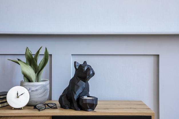 Стильная скандинавская композиция с деревянным комодом, дизайнерским горшком для растений, белыми часами, книгами, кактусами, декором и личными аксессуарами elegnat в современной концепции.