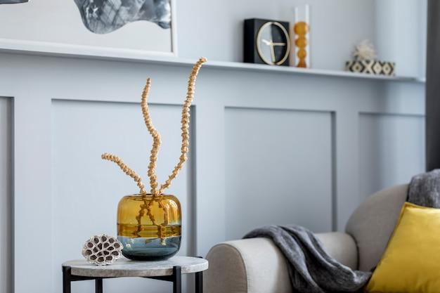 デザイングレーのソファ、アームチェア、大理石のスツール、ブラックコーヒーテーブル、モダンな絵画、装飾、植物、家の装飾のエレガントなパーソナルアクセサリーを備えたリビングルームのスタイリッシュなスカンジナビアの家のインテリア。
