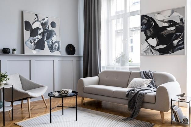Стильный скандинавский домашний интерьер гостиной с дизайнерским серым диваном, креслом, мраморным табуретом, черным журнальным столиком, современными картинами, украшениями, растениями и элегантными личными аксессуарами в домашнем декоре.