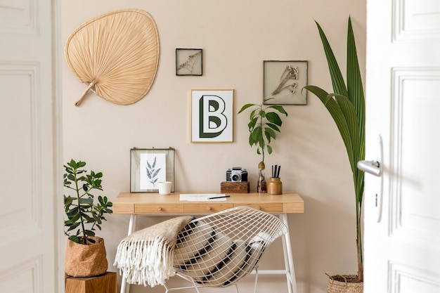 Stylish scandinavian interior of home office space with a lot of photo frames, wooden desk, design chair, plants, office and personal accessories. modern neutral home staging..