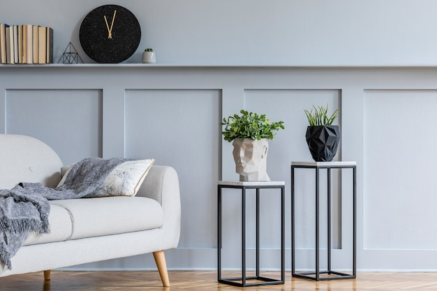 Stylish scandinavian interior of living room with grey sofa, plaid pillows, books, black clock, wood paneling with shelf, marble stools, plants and elegant personal accessories in design home decor.