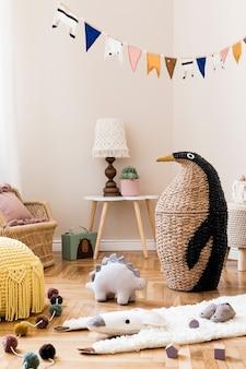 천연 장난감, 매달린 장식, 디자인 가구, 봉제 동물, 테디 베어 및 액세서리가있는 어린이 방의 세련된 스칸디나비아 인테리어. 베이지 색 벽. 아이 방의 인테리어 디자인.