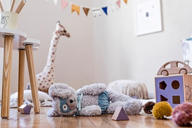 천연 장난감, 매달린 장식, 디자인 가구, 봉제 동물, 테디 베어 및 액세서리가있는 어린이 방의 세련된 스칸디나비아 인테리어. 베이지 색 벽. 아이 방의 인테리어 디자인. .