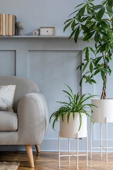 회색 소파, 베개, 책, 금색 시계, 선반이있는 목재 패널, 우아한 개인 액세서리 및 디자인 현대 가정 장식의 식물이있는 거실의 세련된 스칸디나비아 인테리어.