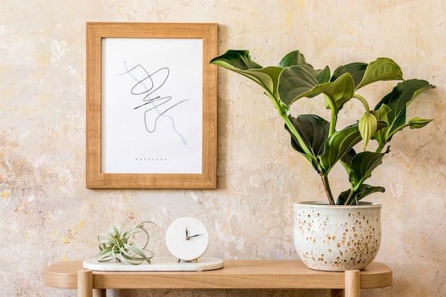 Стильный скандинавский интерьер гостиной с макетом рамки для плаката, деревянной консолью, растениями, часами, декором, стеной в стиле гранж и элегантными личными аксессуарами в современном домашнем декоре.