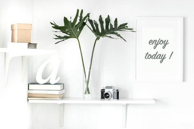 Stylish scandinavian interior with white shelf white mock up poster frame books camera leaves
