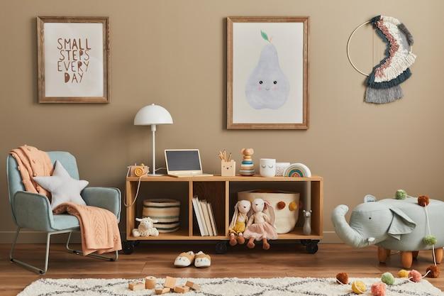 おもちゃ、テディベア、ぬいぐるみ、ミントのアームチェア、家具、装飾品、子供用アクセサリーを備えたスタイリッシュなスカンジナビアの子供部屋のインテリア。壁に茶色の木製ポスターフレーム。