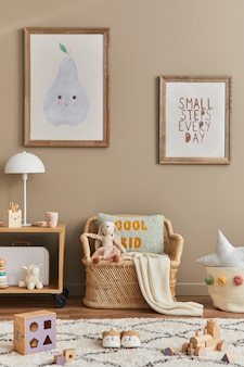 Stylish scandinavian kid room interior with toys, teddy bear, plush animal toys, rattan sofa, furniture, decoration and child accessories. brown wooden frames on the wall. template