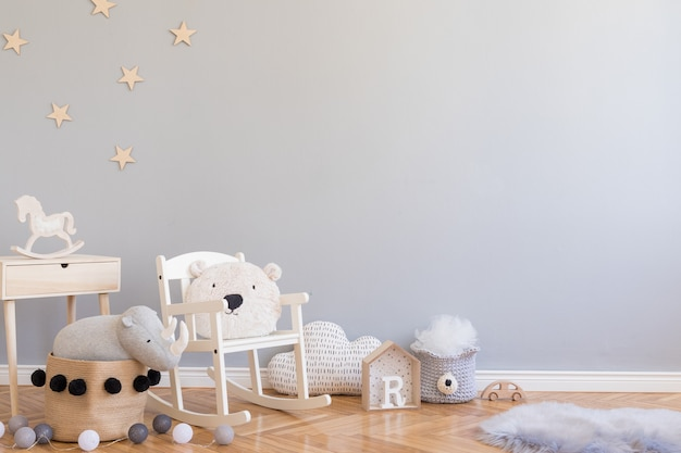 コピースペース、おもちゃ、テディベア、ぬいぐるみ、子供用アクセサリーを備えたスタイリッシュなスカンジナビアの子供部屋。灰色の背景の壁とモダンなインテリア。テンプレート。ホームステージングを設計します。