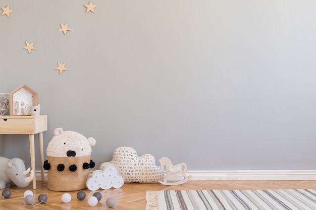 Stylish scandinavian kid room with copy space, toys, teddy bear, plush animal and children accessories. modern interior with grey background walls. template. design home staging.