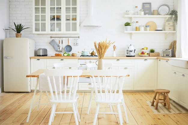Stylish scandinavian kitchen interior: chairs and table in foreground, fridge, long wooden counter with machines, utensils on shelves. interiors, design, ideas, home and coziness concept