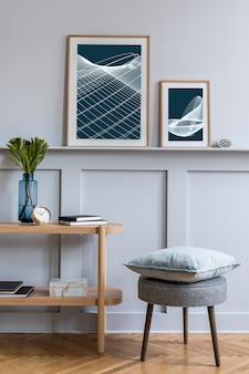 Стильный интерьер гостиной в скандинавском стиле с дизайнерским серым табуретом, рамой для постеров, деревянной консолью, цветком в вазе, книгами, украшениями и элегантными аксессуарами в современном домашнем декоре.