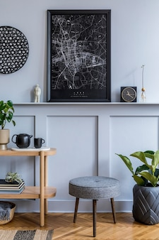 Stylish scandinavian living room interior with design grey stool, wooden console, plants, book, decoration, mock up poster frame on the shelf and elegant accessories in modern home decor.
