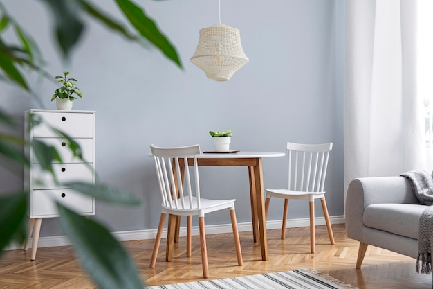 창의적인 나무 책상, 회색 소파, 대나무 책꽂이, 책, 식물 및 디자인 가정 장식의 우아한 장식을 갖춘 세련된 스칸디나비아 거실