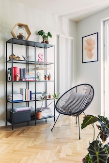 Stylish scandinavian living room with design armchair and bookstand with accessories