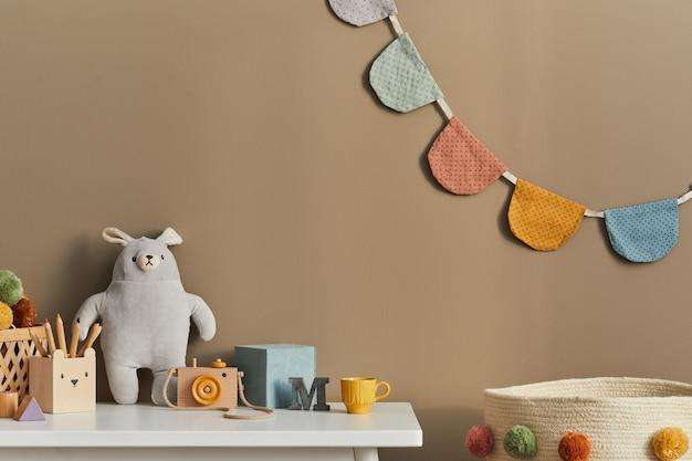 コピースペースのおもちゃの豪華な動物と子供のアクセサリーを備えたスタイリッシュなスカンジナビアの新生児の部屋居心地の良い装飾とベージュの壁にぶら下がっている綿の旗