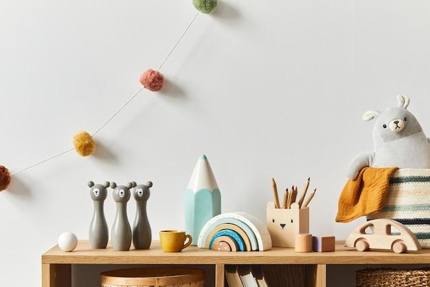 장난감, 봉제 동물, 사진 카메라 및 어린이 액세서리가있는 세련된 스칸디나비아 신생아 방입니다. 아늑한 장식과 흰 벽에 목화 공을 걸려. 공간을 복사하십시오.
