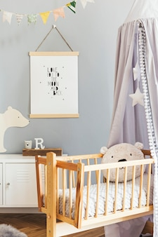 Stylish scandinavian nursery interior with hanging mock up poster, grey canopy with stars and white shelf with cloud pillow, natural basket and children's accessories. grey background wall.