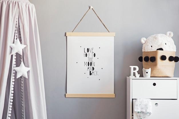 포스터가 걸려있는 세련된 스칸디나비아 보육원 인테리어, 별이있는 회색 캐노피, 구름 베개가있는 흰색 선반, 천연 바구니 및 어린 이용 액세서리