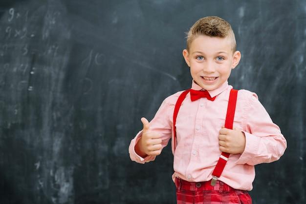 Stylish schoolboy gesturing thumbs up