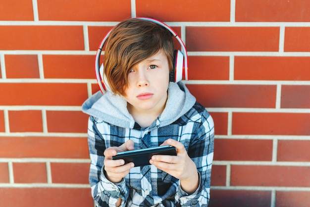 Stylish schoolboy with smartphone and headphones listening to music or playing game over brick wall. leisure, children, technology and people concept