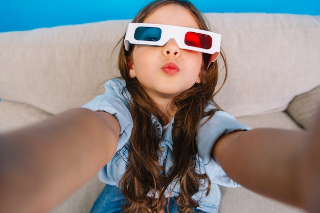 Stylish selfie portrait of charming little girl in 3d glasses sending a kiss to camera. chilling on couch on blue background, wearing jeans clothes, long brunette hair, expressing happiness