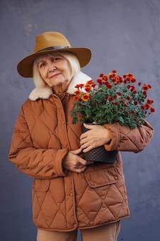 Стильная старшая дама с цветочным горшком. довольная пожилая женщина в модной шляпе и теплой куртке