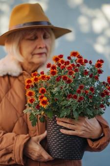Стильная старшая дама с цветочным горшком. пожилая женщина в шляпе и теплой куртке несет горшок с цветами