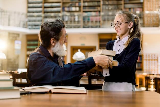 Стильный старший мужчина дедушка или учитель сидит за столом в старой древней библиотеке и берет книги у своей симпатичной внучки или ученицы