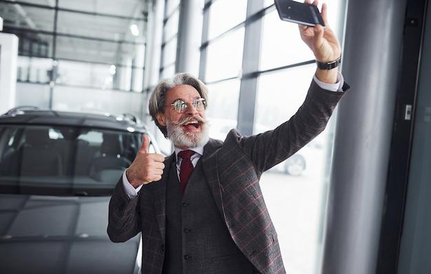 정장을 입고 수염을 기른 세련된 노인은 현대적인 새 차를 배경으로 셀카를 찍습니다. 엄지손가락을 보여줍니다.