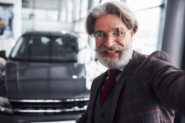 정장을 입고 수염을 기른 세련된 노인은 현대적인 새 차를 배경으로 셀카를 찍습니다.