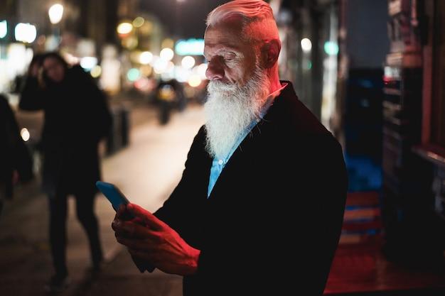 Стильный пожилой мужчина с помощью смартфона стоит на городской улице с огнями боке на заднем плане - влиятельный хипстерский авторитет, развлекающийся с технологическими тенденциями - технологии и радостный пожилой образ жизни - сосредоточение внимания на лице