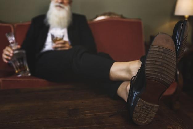 검은 가죽 신발을 착용하는 세련 된 수석 남자