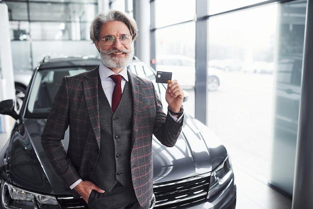 회색 머리와 수염을 기른 세련된 노인은 신용카드를 들고 현대적인 검은색 차를 마주하고 있습니다.