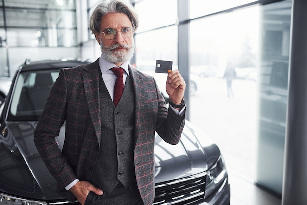 Stylish senior man with gray hair and beard stands against modern black car with credit card in hand.