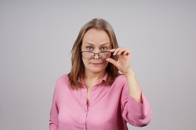 ピンクのブラウスを着たスタイリッシュな年配の女性がメガネを持っています