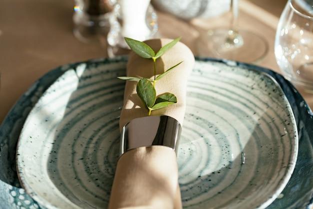 Стильная сервировка на зеленой керамической тарелке с хлопковой салфеткой