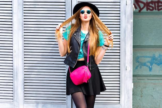 スタイリッシュなセクシーなブロンドの女性が通りでポーズ、流行に敏感な明るい服装、遊び心のあるクールな感情、楽しい、楽しんで、一人で幸せな休暇を過ごす、ヴィンテージハットとミニスカート。