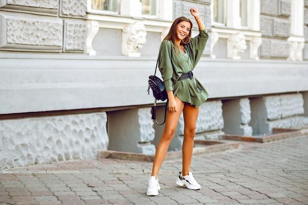 Стильная сексуальная веселая великолепная девушка-модель позирует на улице