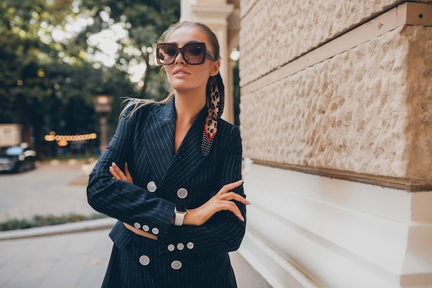 Stylish sexy woman dressed in elegant tuxedo suit walking in city on summer autumn day